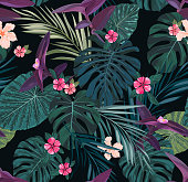 Seamless botanical exotic vector pattern with green palm leaves and hibiscus flowers on dark background