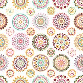 Seamless pattern of bright colorful geometric round ethnic decorative elements.