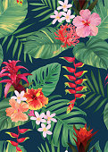 Seamless tropical pattern with guzmania, hibiscus flowers and palm leaves background.