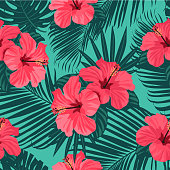 Seamless tropical vector pattern with bright hibiscus flowers and exotic palm leaves on background.
