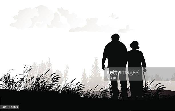 Senior Couple Walking In A Field