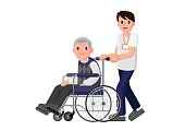 Senior man in wheelchair with a careful man. Young volunteer caring for elderly man.