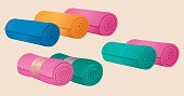 Set of rolled blankets, comforters or duvets, gymnastic mats.