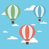 Set of three colorful hot air balloons of red green and blue colors with a basket and ropes flying high after a bright blue sky with white clouds - Vector