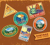 Set of vintage luggage travel stickers on aged leather texture
