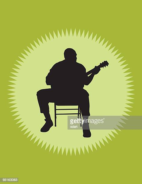 Shadow of male guitarist sitting on a chair playing guitar