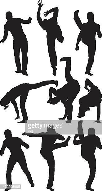 Shirtless young man practicing capoeira