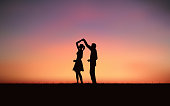 Silhouette couple man and woman dancing on hill under sunset sky background