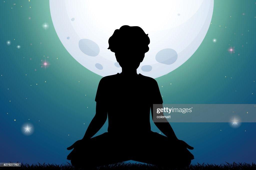 Silhouette man meditating in park at night