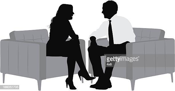 Silhouette of a business couple sitting on armchair