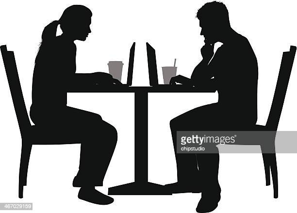 A silhouette of a couple using a laptop