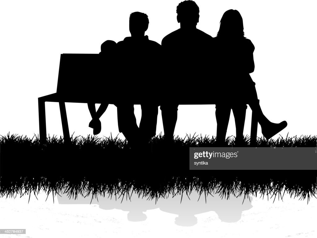 A silhouette of a family sitting on a bench outside