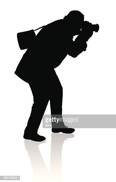 silhouette of a photographer in action - camera stand stock illustrations, clip art, cartoons, & icons