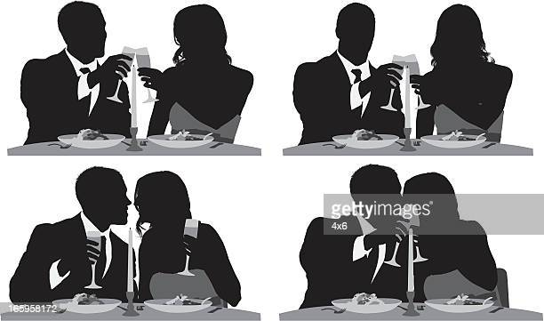 Silhouette of a romantic couple at dinner