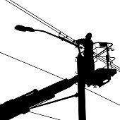 Silhouette of an electrician working on a street light