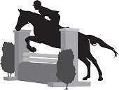 Silhouette of an equestrian rider and horse jumping a fence