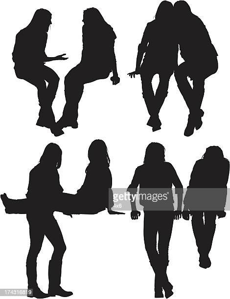 silhouette of female friends - legs crossed at ankle stock illustrations