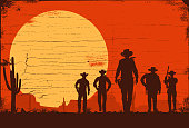 Silhouette of five cowboys walking forward on a wooden board