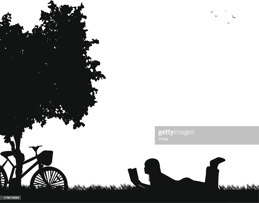 Silhouette of girl reading a book under the tree