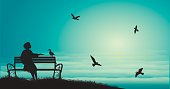 silhouette of girl sitting on the bench near the sea with sun-rise and feed the sea gulls, shadows, memories,