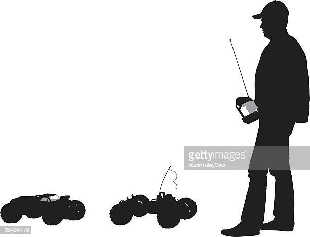 Silhouette of man with radio controls and two small cars