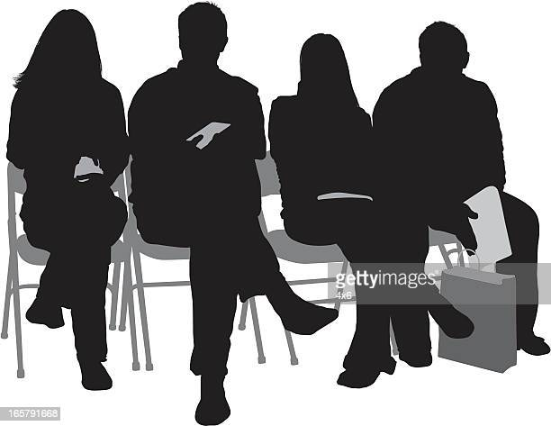 Silhouette of people sitting on chairs