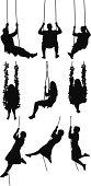 Silhouette of people swinging on swings