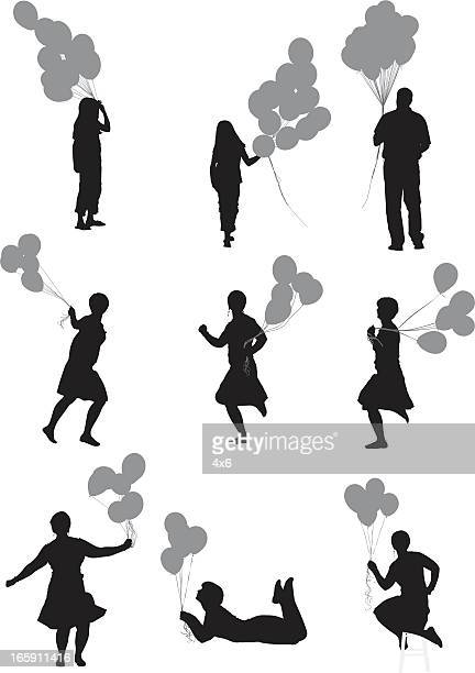 Silhouette of people with balloons