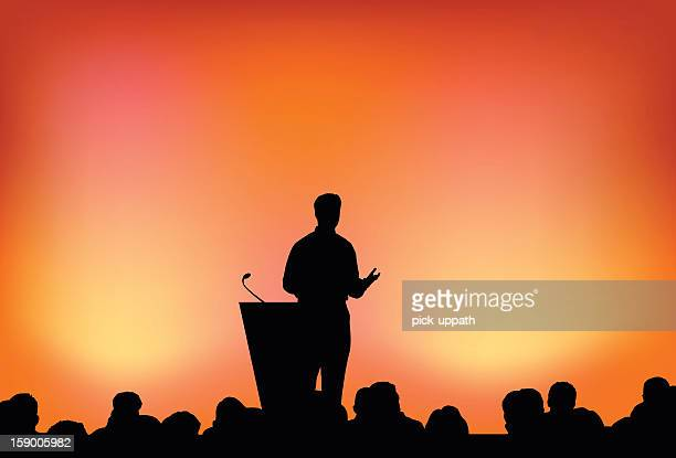 Silhouette of person presenting in front of crowd