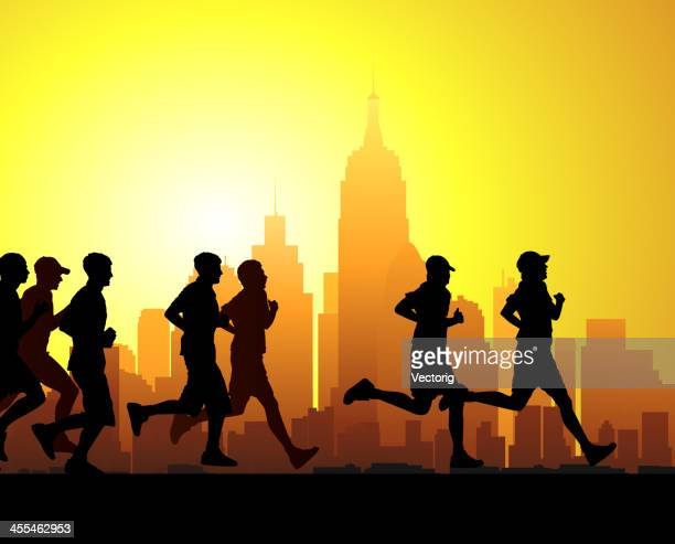 Silhouette of race runners in front of sunset lit cityscape