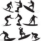 Silhouette of surfers in action