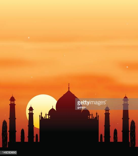 Silhouette of the Taj Mahal in front of orange sunset sky