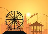 Silhouettes of a city and amusement park .