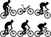 Silhouettes of carbon fiber full suspension mountain bike with cyclists