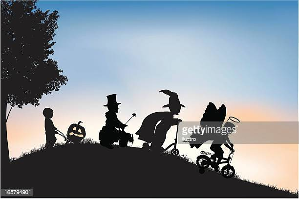Silhouettes of children dressed up for Halloween outside