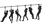 Silhouettes of children playing with a tyrolean traverse