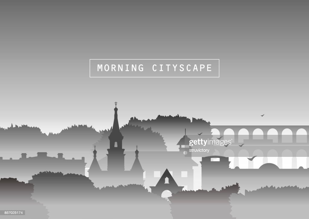 Silhouettes of church, old houses, trees and bridge in fog.