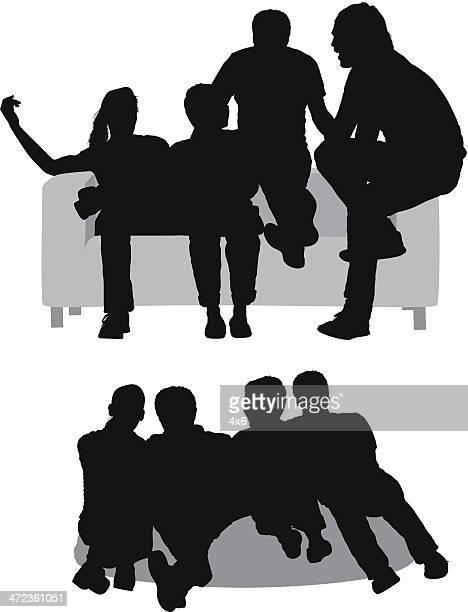 Silhouetten von Freunden sitzen auf couch