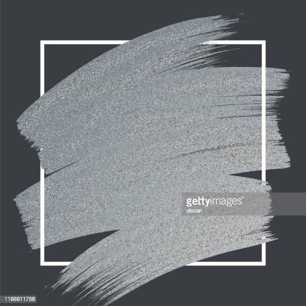 silver glitter paint brush stroke with frame on black background. - silver coloured stock illustrations