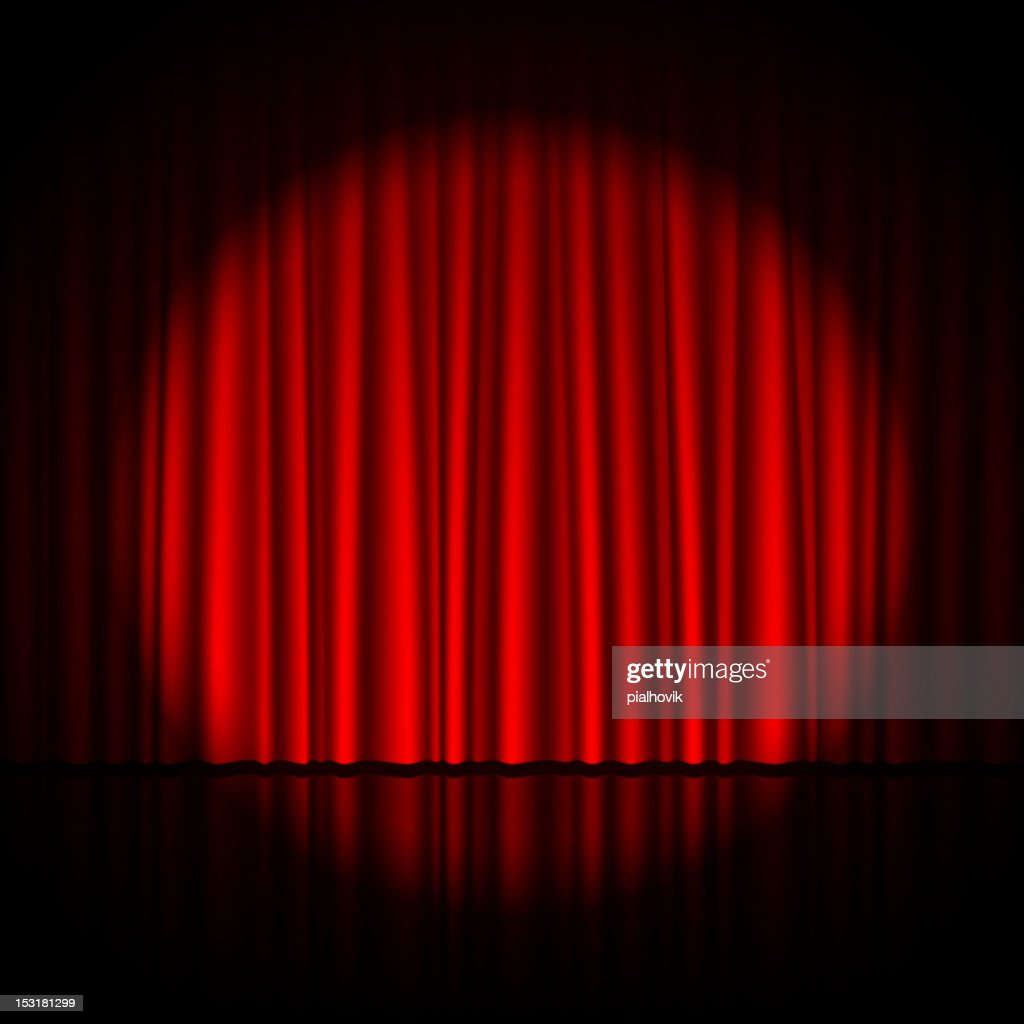 Single spotlight shining on pleated red theatrical curtains
