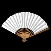 A single tan and white fan on a black background