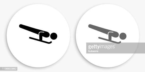 skelett schlitten schwarz und weiß runde symbol - skeleton wintersport stock-grafiken, -clipart, -cartoons und -symbole