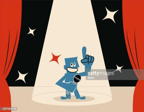 stockillustraties, clipart, cartoons en iconen met lachend blauw man (host) op het podium met microfoon en spotlight - winners podium