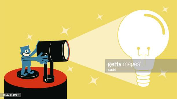 Smiling blue man with spotlight and spotlit idea light bulb