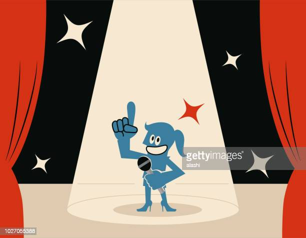 smiling blue woman (host) on stage with microphone and spotlight - game show host stock illustrations
