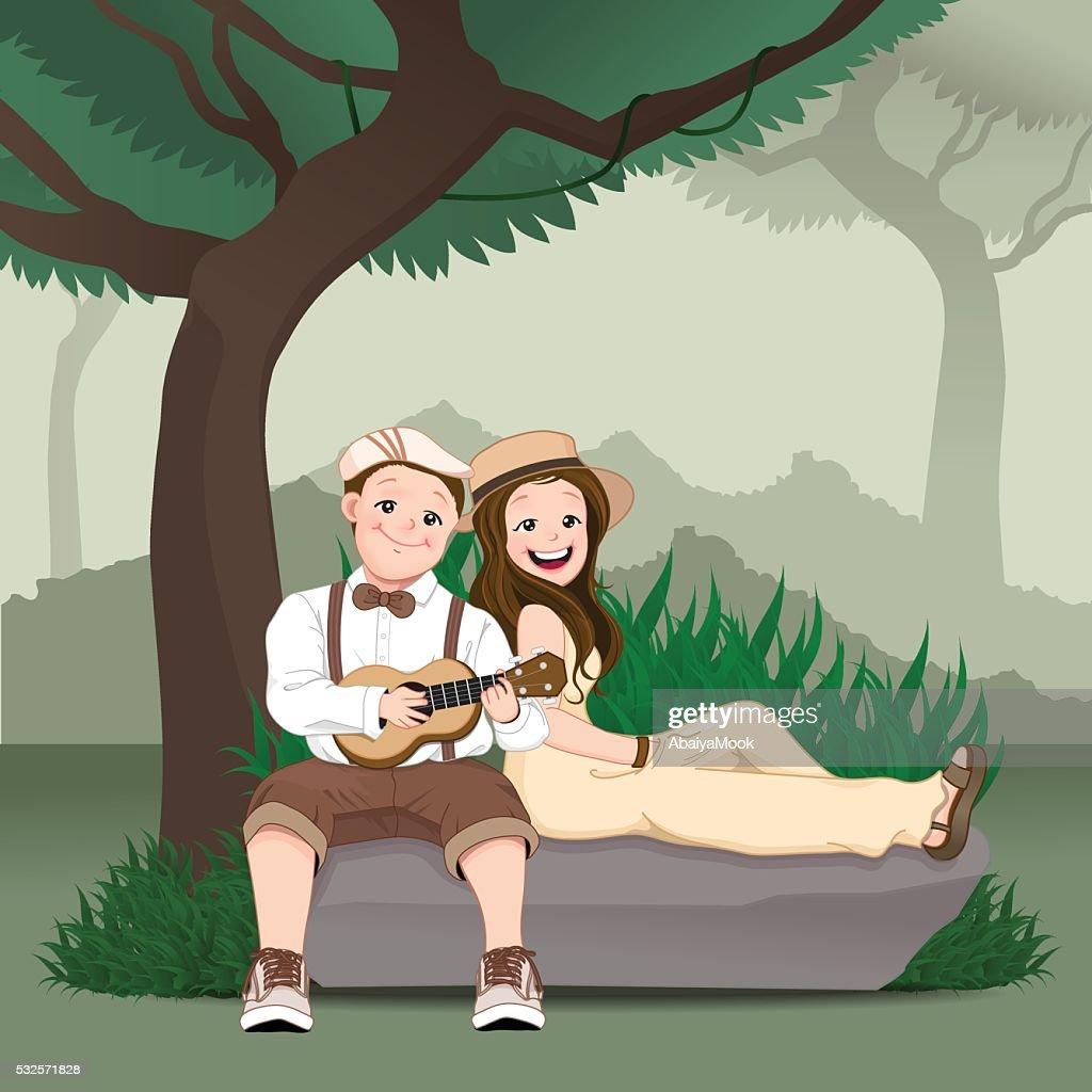 Smiling couple sitting on the rock and playing ukulele