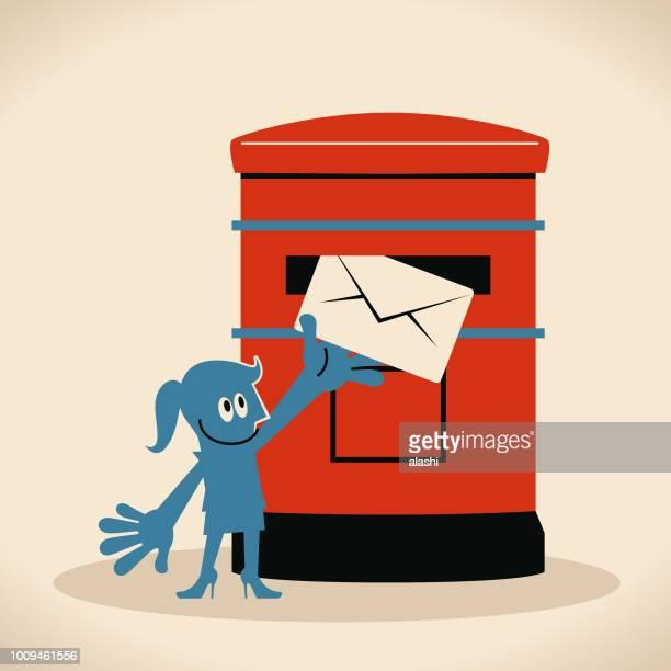 Femme souriante mettant une enveloppe dans une boîte aux lettres publique, envoi de courrier ou la carte postale