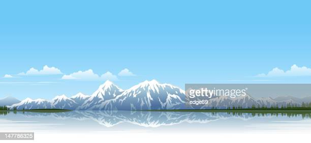 Snow topped mountain range by the lake