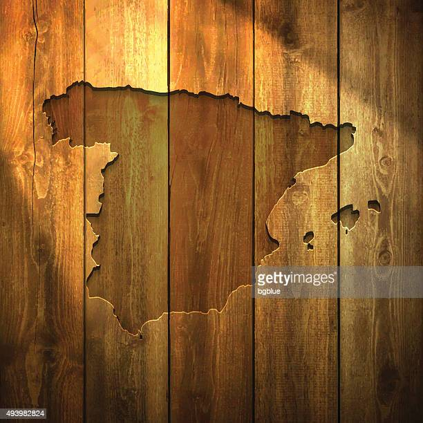 spain map on lit wooden background - iberian peninsula stock illustrations, clip art, cartoons, & icons