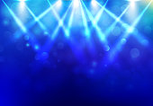 Spotlights lighting disco party stage with blured bokeh on blue dark background.